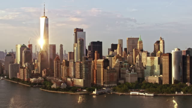 aerial freedom tower in lower manhattan reflektiert die sonne - one world trade center stock-videos und b-roll-filmmaterial