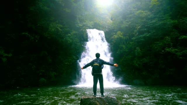freedom travel,man standing and raising arm in front of waterfall - waterfall stock videos & royalty-free footage