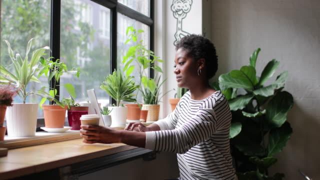 stockvideo's en b-roll-footage met freelance african american businesswoman working in a cafe - flexplekken