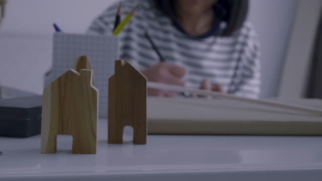 Freelance Asian Women Working at home (Make a house model)