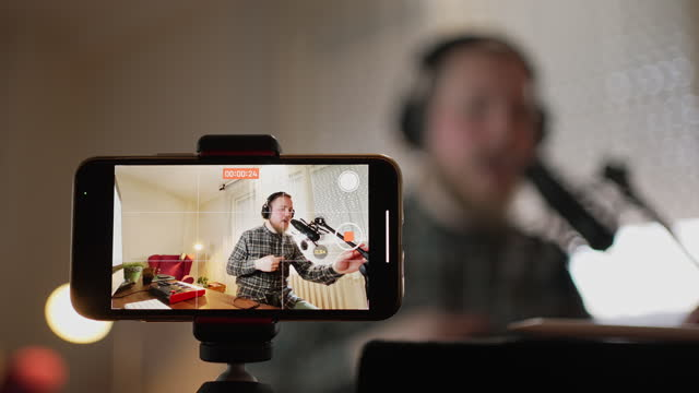 freelance musician, going live on his vlog while singing and using the audience to present his new song - content stock videos & royalty-free footage