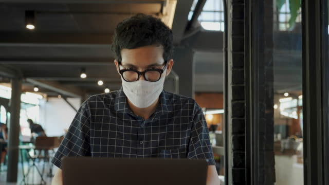 freelance putting protective face mask using laptop at cafe - study stock videos & royalty-free footage