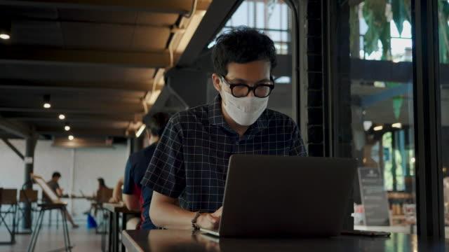 vídeos de stock e filmes b-roll de freelance putting protective face mask using laptop at cafe - inteligência