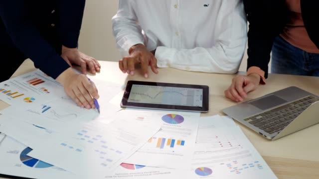 stockvideo's en b-roll-footage met freelance team maken en analisten vergadering grafieken en grafieken en brainstormen, langzame motie - report document