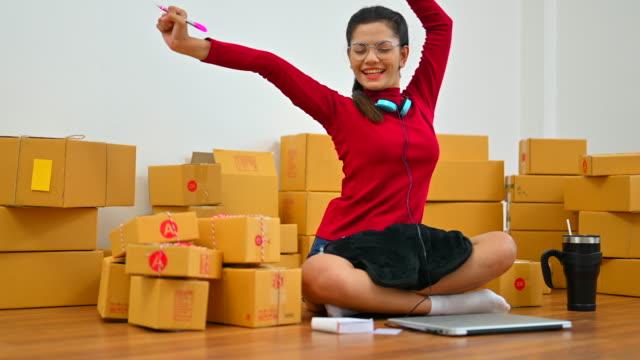 box、ヤングビジネスオーナーのホームオフィス、オンラインマーケティングパッケージングボックスとデリバリー、sme、デリバリー e コマースのコンセプトで働く sme フリーランス女性。小� - ビジネスカジュアル点の映像素材/bロール