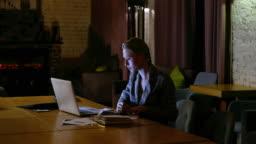 freelancer girl works at laptop in evening