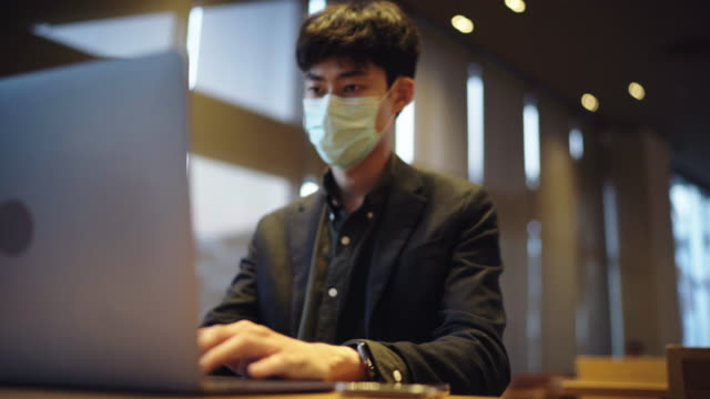 freelancer man using pollution mask for using laptop at coffee shop - refreshment stock videos & royalty-free footage