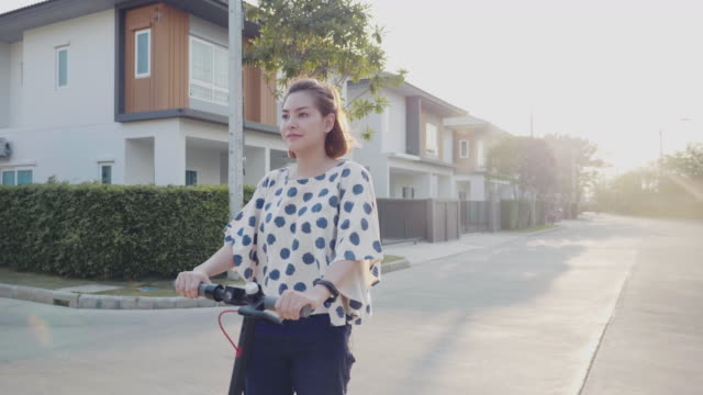 freelancer riding motor scooter go to work at park - motor video stock e b–roll