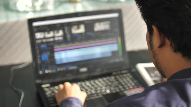 freelancer video editor works at the laptop - using laptop stock videos & royalty-free footage