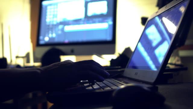 vídeos de stock e filmes b-roll de freelancer video editor works at the laptop - editorial