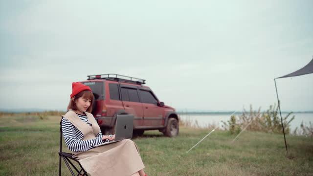 週末にキャンプテントに座ってラップトップを使用して働くフリーランサーの女性 - キャンプする点の映像素材/bロール