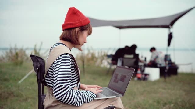 vídeos de stock, filmes e b-roll de mulher freelancer trabalhando usando laptop sentado em uma tenda de camping no fim de semana - computador desktop