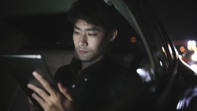 en frilansare som arbetar på tabletten i bilen på natten - taxi bildbanksvideor och videomaterial från bakom kulisserna