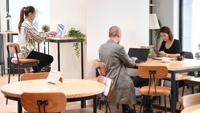 vidéos et rushes de freelancers travaillant dans l'espace de coworking de bureau ouvert - hot desking