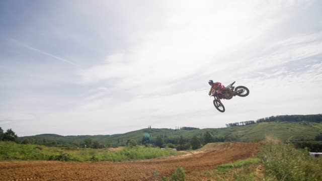 freestyle motocross rider jumping over a dirt ramp, performing a stunt - off road racing stock videos & royalty-free footage