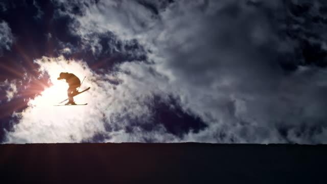 slo-mo-ld-freestyle-skifahrer in der luft in der half-pipe mit sonne im hintergrund - freistil skifahren stock-videos und b-roll-filmmaterial