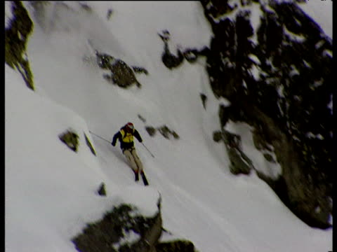 freestyle skier negotiates way down steep rocky mountainside before racing through the finishing posts raised arms in celebration engadin mountain... - human limb stock videos & royalty-free footage