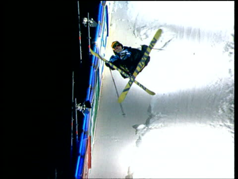 Freestyle skier performs aerial off ski jump then lands backwards onto snow