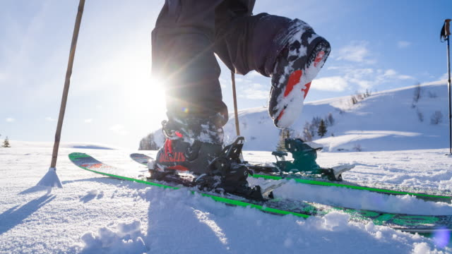Freestyle skier putting on skis