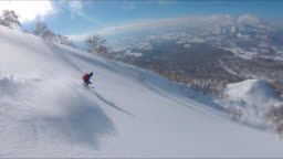 DRONE: Freestyle skier shredding the snow while riding in the scenic mountains.