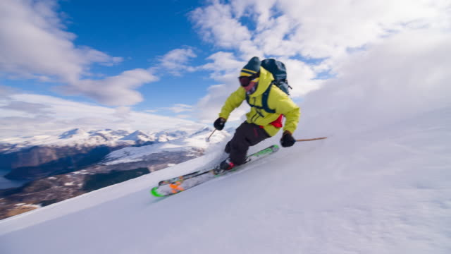 freestyle skier skiing powder snow with a fjord in background - skiing stock videos & royalty-free footage