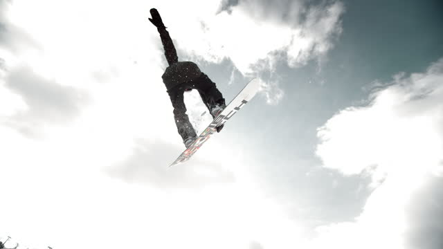 slo mo ts freestyle snowboarder doing a grab on big air jump - snowboard video stock e b–roll