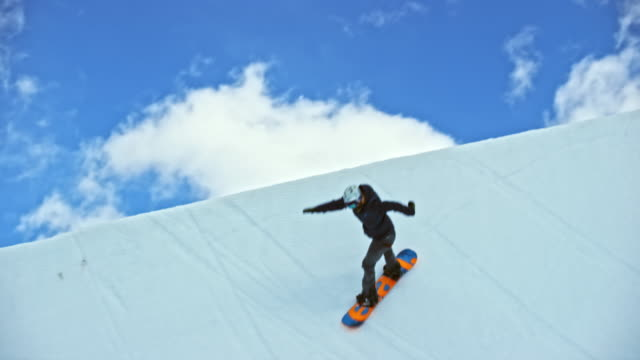 slo mo freestyle snowboarder jumping in the air in the half-pipe - wide stock videos and b-roll footage