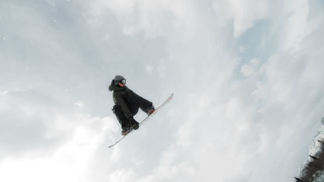 SLO MO TS Freestyle snowboarder performing grab and spin trick
