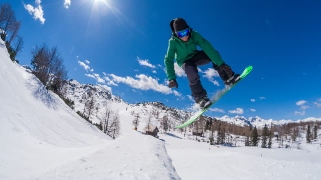 Freestyle snowboarder performing jump stunt in a snow park