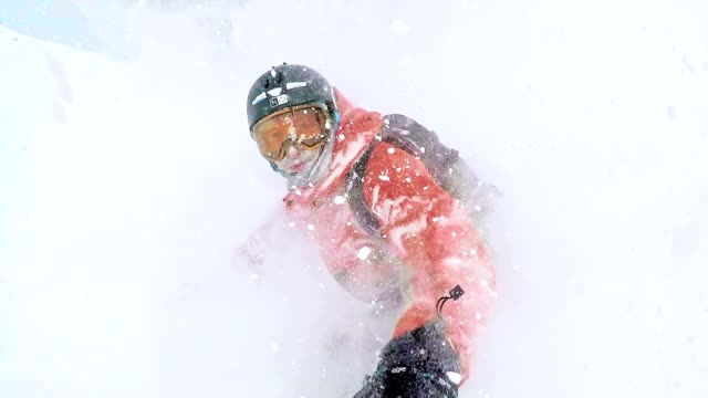 Freestyle snowboarders skiing down the hill in snowy weather