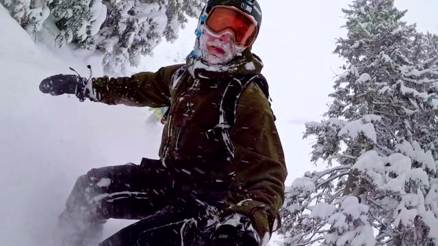 Freestyle snowboarders skiing through forest in snow storm