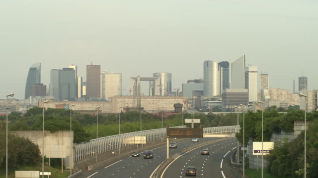 WS freeway and office buildings of La Defense with the Grande Arche in center and the Eiffel Tower visible in the distance on the right