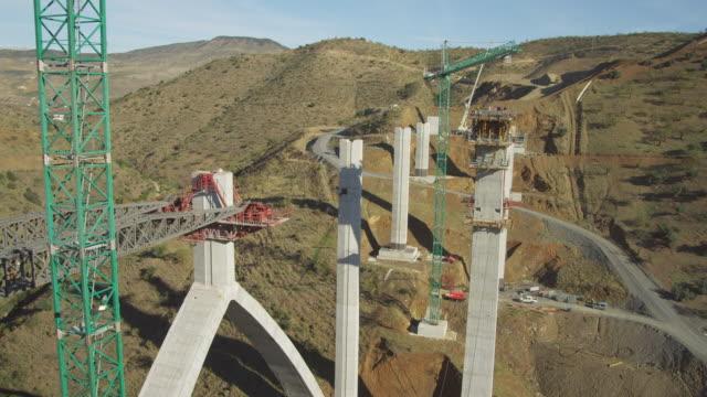 ws ha freeway bridge construction site, view from man rider suspended from crane - コンクリート点の映像素材/bロール