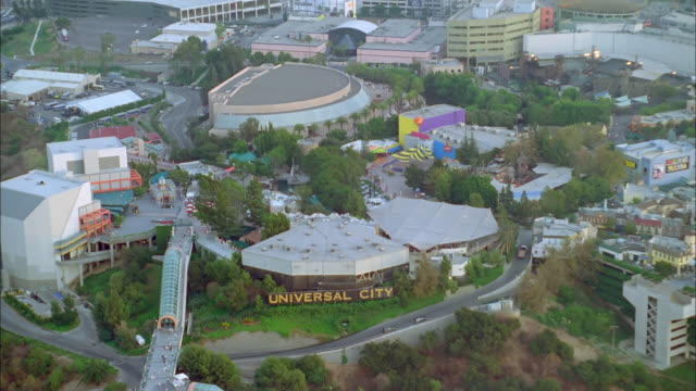 a freeway encircles the universal city amusement park. available in hd. - universal city video stock e b–roll