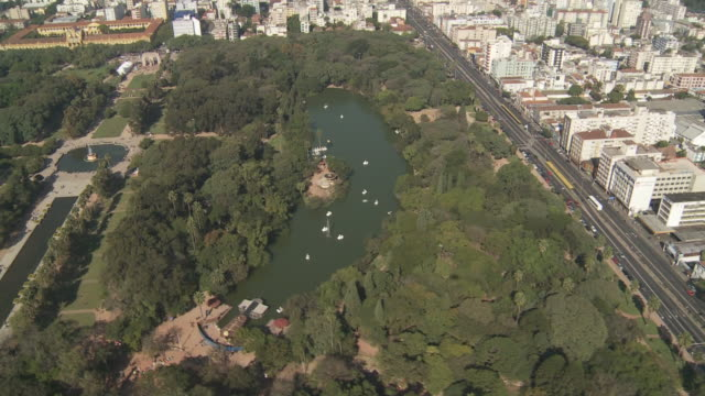 A freeway passes a wooded park and lake in Porto Alegre, Brazil.