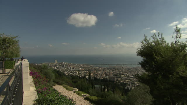 a freeway passes haifa toward the ocean where a few ships moor off the coast. - haifa video stock e b–roll