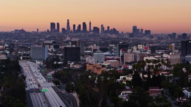 vidéos et rushes de freeway 101 passé hollywood au lever du soleil - statique drone shot - hollywood california