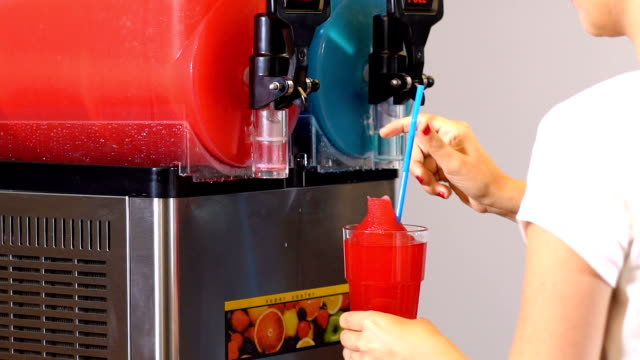freezing and mixing machine for the production of cold ice slush fruit juice. different flavors in many colors. slow motion, - frozen yogurt stock videos and b-roll footage