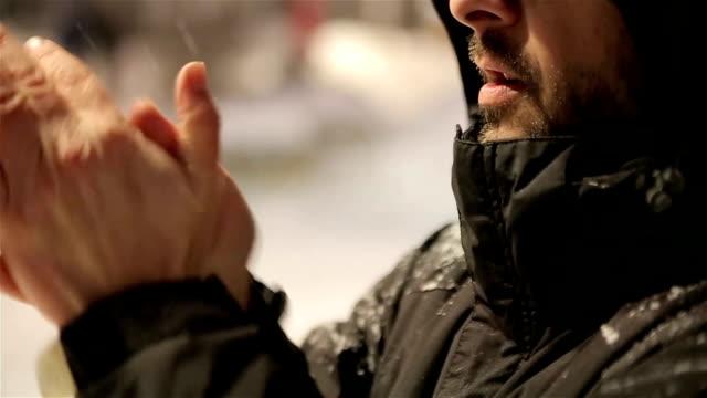 Gel homme froid dans la tempête de neige blanche à essayer de garder au chaud en soufflant dans ses mains