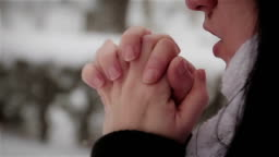 Freezing cold women in snow storm white out trying to keep warm by blowing into his hands