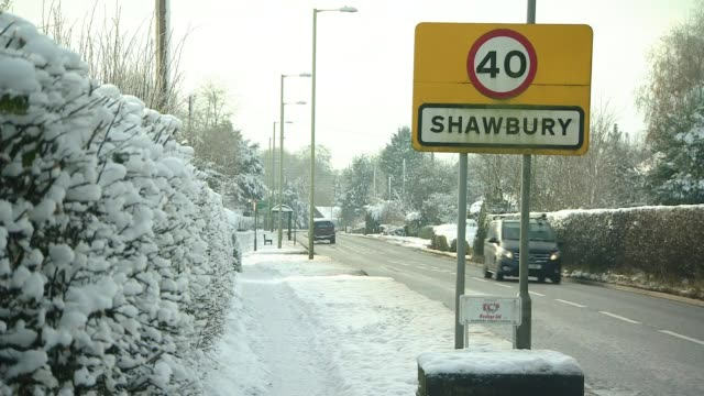 freezing conditions continue across the country; england: shropshire: shawbury: ext / snow 'shawbury' name sign at roadside - traffic passing car... - street name sign stock videos & royalty-free footage