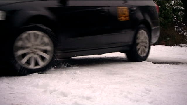 freezing weather causes hazardous driving conditions road sign warning of snow placed next to snow covered road as traffic along leeds car sliding as... - eurostar stock-videos und b-roll-filmmaterial
