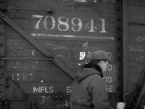 Freight cars in train yard male stapling destination tags onto freights Switchman Warren Gordon Scott signaling to engineer to move locomotive to...