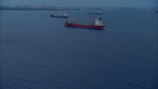 aerial freight ship anchored near freeport at dusk, bahamas - anchored stock videos & royalty-free footage