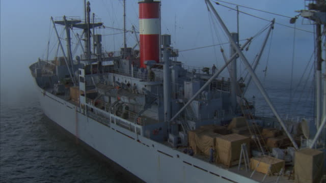 low aerial freight ship emerging from fog - netting stock videos and b-roll footage