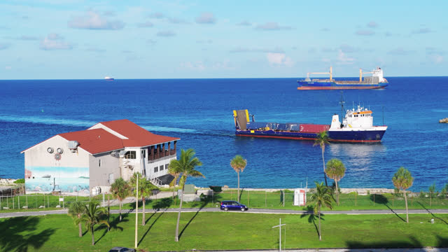 freight ship enters the bay of water in the city port on july 20, 2019; in freeport, bahamas. the building to the left is a seafood restaurant.... - horizon over water stock videos & royalty-free footage
