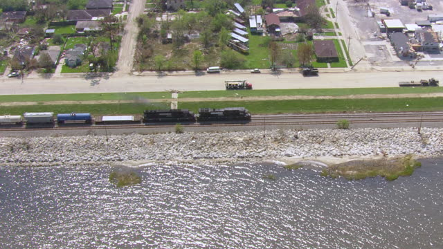 Freight train along Lake Pontchartrain in destructed suburban area / United States