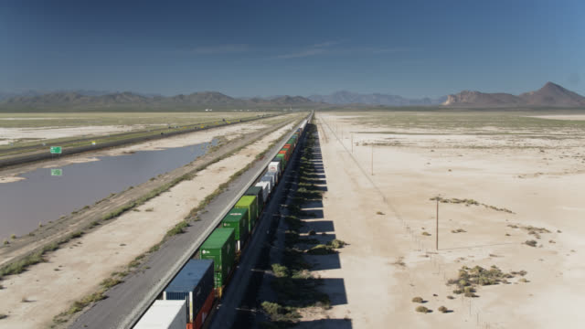 freight train alongside i-10 freeway in southern new mexico - freight train stock videos & royalty-free footage