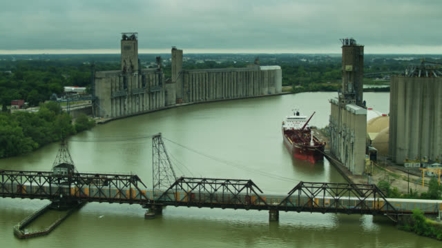 freight train and cargo ship at grain elevators in toledo, ohio - aerial - freight elevator stock videos & royalty-free footage