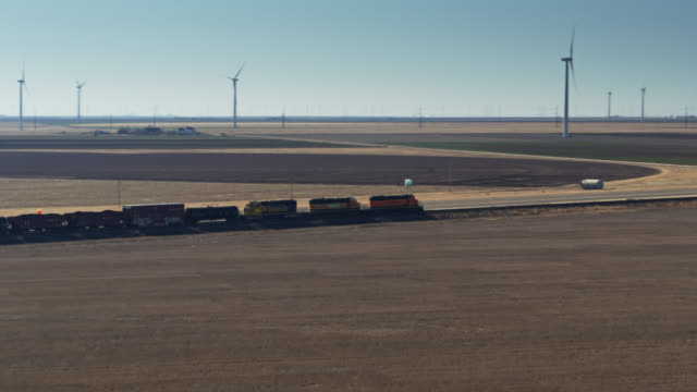 freight train and road passing wind farm in texas panhandle - aerial - propeller stock videos & royalty-free footage